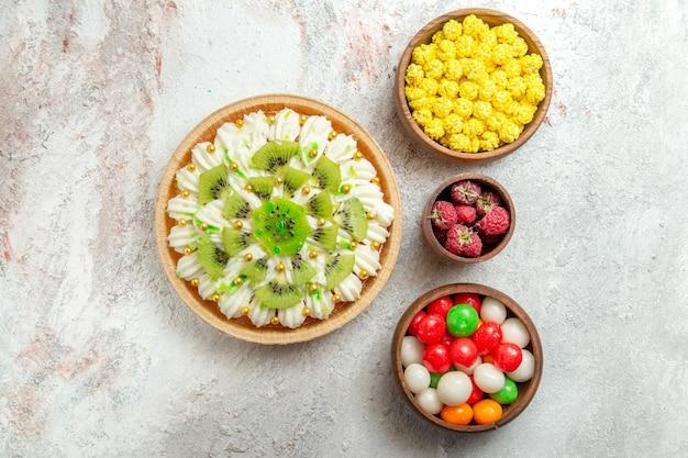 Vista superior deliciosa sobremesa de kiwi com doces no fundo branco sobremesa bolo creme fruta tropical