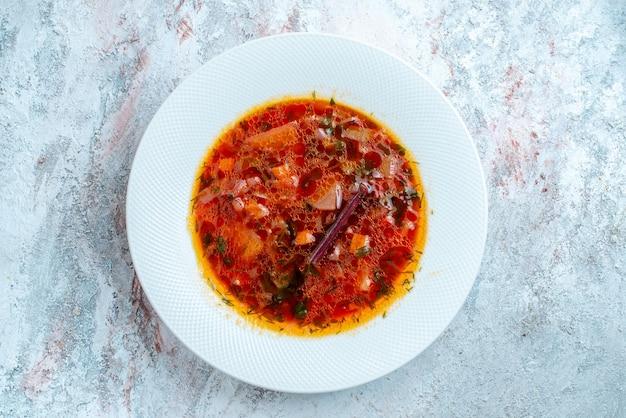 Vista superior deliciosa sopa de beterraba ucraniana famosa borsch com carne dentro do prato em um espaço em branco claro