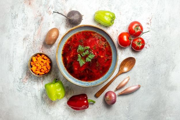 Vista superior deliciosa sopa de beterraba ucraniana famosa de borsch no chão branco sopa de vegetais comida jantar