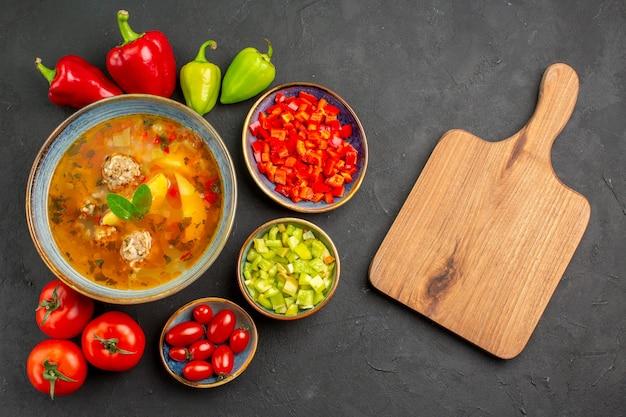 Vista superior deliciosa sopa de carne com legumes frescos em piso escuro prato foto refeição