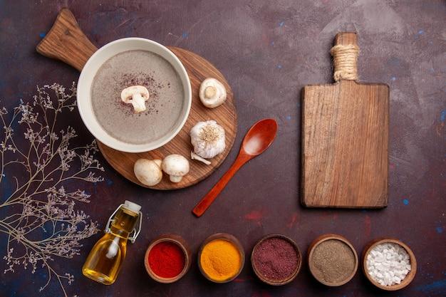Vista superior deliciosa sopa de cogumelos com diferentes temperos na mesa escura