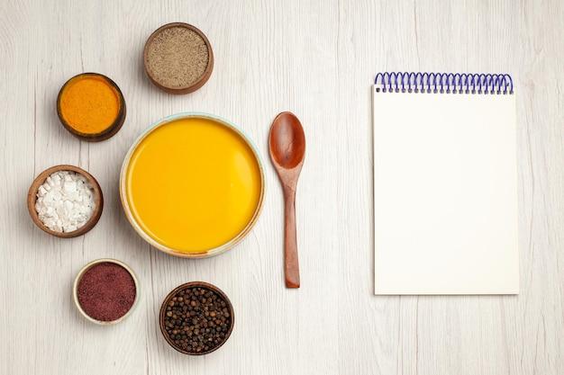 Vista superior deliciosa sopa de creme com diferentes temperos em mesa de madeira branca sopa de molho refeição creme prato jantar