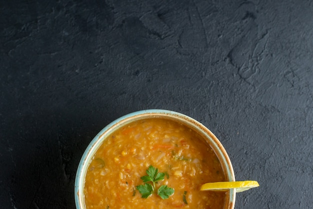 Vista superior deliciosa sopa de lentilha com rodela de limão dentro do prato em superfície escura