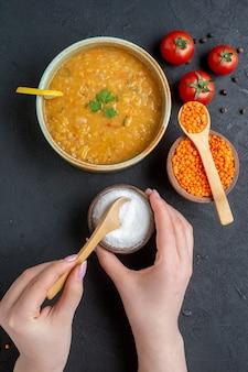 Vista superior deliciosa sopa de lentilha com sal saindo do pratinho e tomates vermelhos na superfície escura