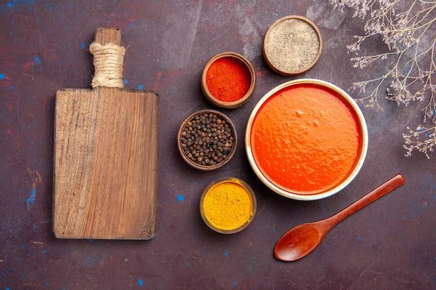 Vista superior deliciosa sopa de tomate cozida com tomates frescos com temperos no fundo escuro refeição com molho de prato de tomate sopa