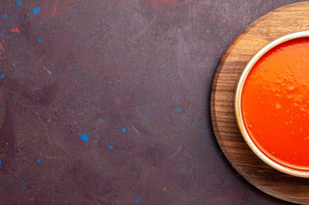 Vista superior deliciosa sopa de tomate cozido com tomates vermelhos frescos em fundo escuro prato de sopa de tomate molho refeição