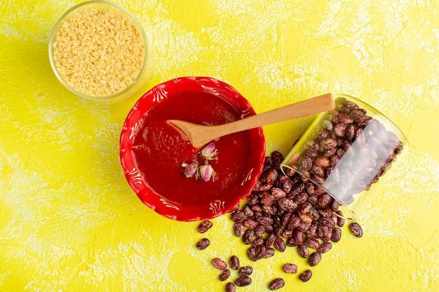 Vista superior deliciosa sopa de tomate dentro de um prato vermelho com feijão cru na mesa amarela, refeição de sopa, jantar, comida vegetal