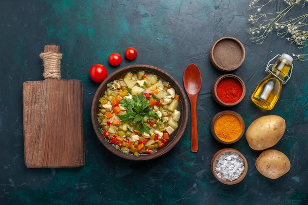 Vista superior deliciosa sopa de vegetais com azeite de oliva e diferentes temperos em fundo azul escuro ingrediente sopa de vegetais óleo de salada