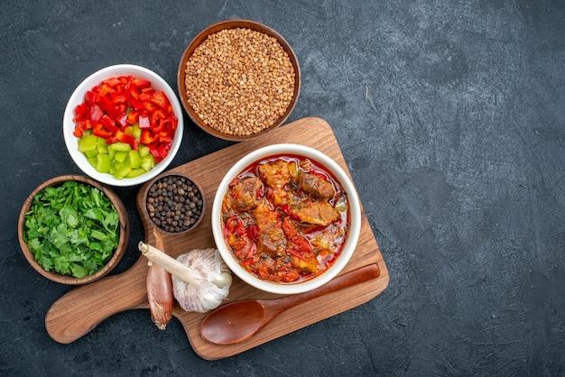 Vista superior deliciosa sopa de vegetais com trigo sarraceno cru e verduras no espaço cinza