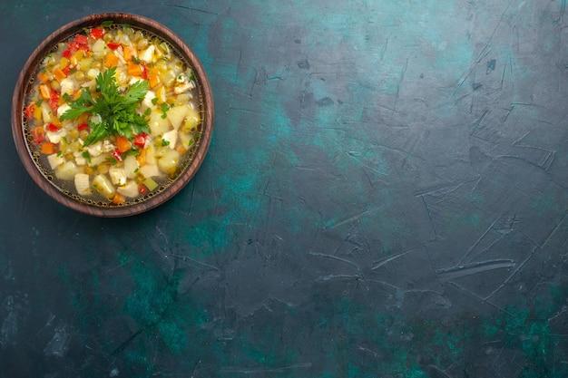 Vista superior deliciosa sopa de vegetais com vegetais fatiados e verduras no fundo azul escuro