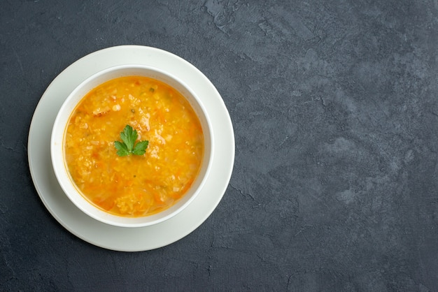 Vista superior deliciosa sopa dentro de um prato branco em uma superfície escura