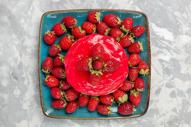 Vista superior deliciosa torta de bolo com creme vermelho e morangos frescos na superfície branca bolo biscoito assar creme açúcar