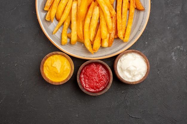 Vista superior deliciosas batatas fritas com temperos no fundo escuro prato de batata refeição hambúrguer fast-food