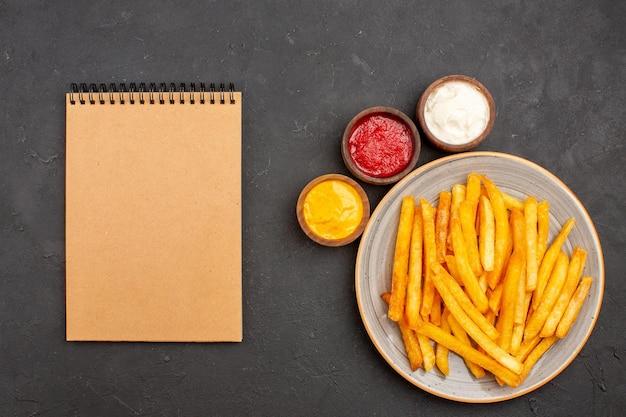 Vista superior deliciosas batatas fritas com temperos no fundo escuro refeição fast-food hambúrguer prato de batata