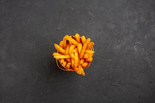 Vista superior deliciosas batatas fritas dentro da embalagem no fundo escuro refeição de hambúrguer com prato de batata fast-food