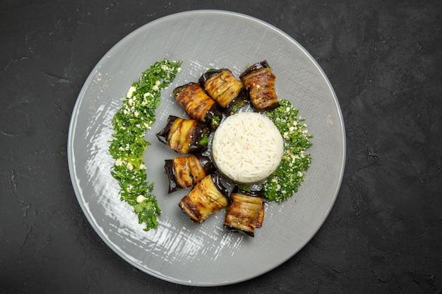 Vista superior deliciosas berinjelas cozidas com verduras e arroz na superfície escura jantar farinha de arroz com óleo de cozinha