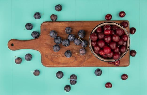 Vista superior deliciosas cerejas vermelhas em uma tigela sobre uma placa de cozinha de madeira com abrunhos isolados em um fundo azul