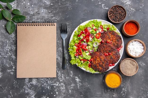Vista superior deliciosas costeletas de carne com salada e temperos em um prato de comida com foto de fundo cinza