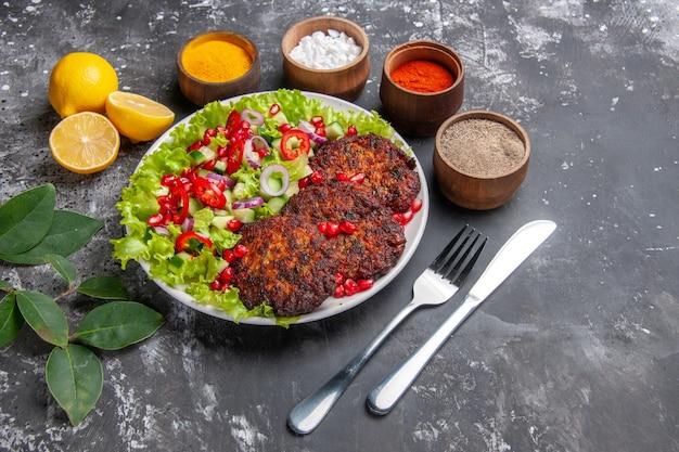 Vista superior deliciosas costeletas de carne com salada e temperos em um prato de fundo cinza