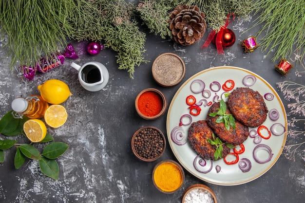 Vista superior deliciosas costeletas de carne com temperos no prato de fundo cinza claro com fotos