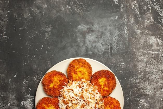 Vista superior deliciosas costeletas fritas com arroz cozido em prato de superfície escura foto refeição