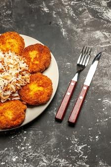 Vista superior deliciosas costeletas fritas com arroz cozido em prato escuro de mesa.