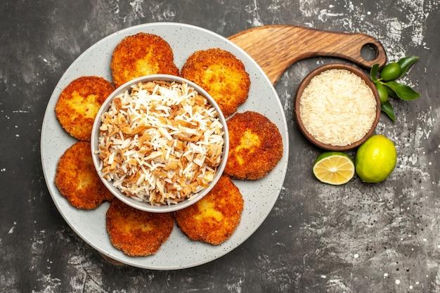 Vista superior deliciosas costeletas fritas com arroz cozido em um prato de carne rissole de superfície escura