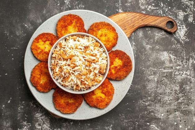 Vista superior deliciosas costeletas fritas com arroz cozido em um prato de rissole de carne de superfície escura