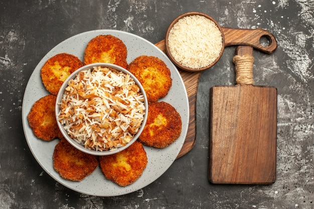 Vista superior deliciosas costeletas fritas com arroz cozido em um prato de rissole de superfície escura