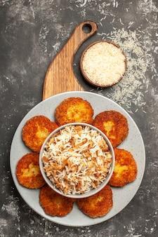 Vista superior deliciosas costeletas fritas com arroz cozido em um prato escuro de rissole de carne