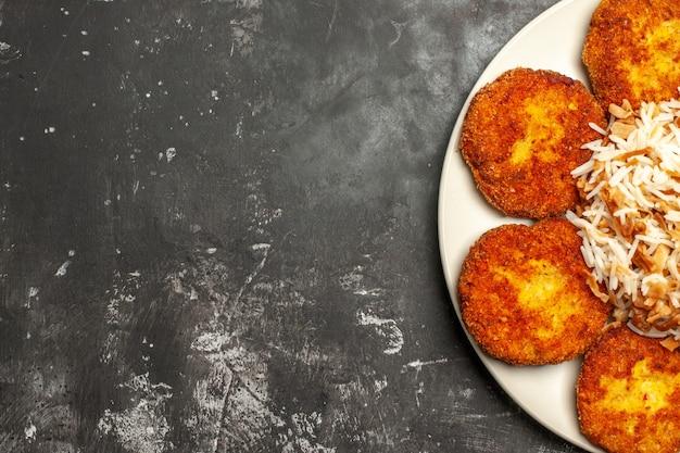 Vista superior deliciosas costeletas fritas com arroz cozido em uma refeição de prato de carne de superfície escura