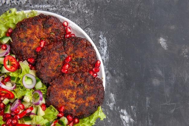 Vista superior deliciosas costeletas fritas com salada fresca