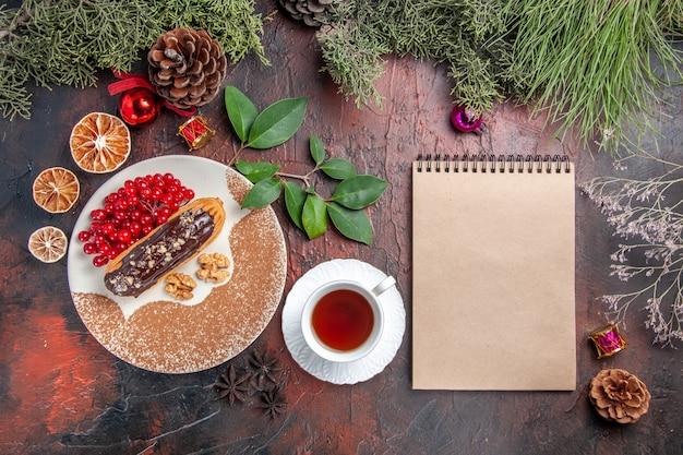 Vista superior deliciosas eclairs de chocolate com chá e frutas vermelhas na mesa escura, bolos doces, torta e sobremesa