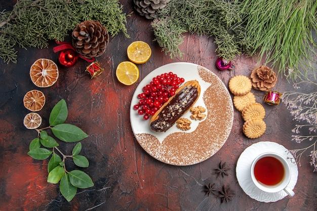Vista superior deliciosas eclairs de chocolate com chá e frutas vermelhas no chão escuro, torta de bolo doce e sobremesa