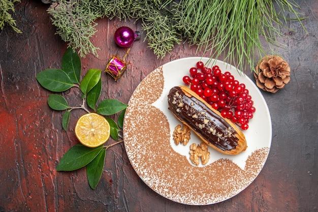 Vista superior deliciosas eclairs de chocolate com frutas vermelhas na mesa escura, torta, bolo, sobremesa, doce