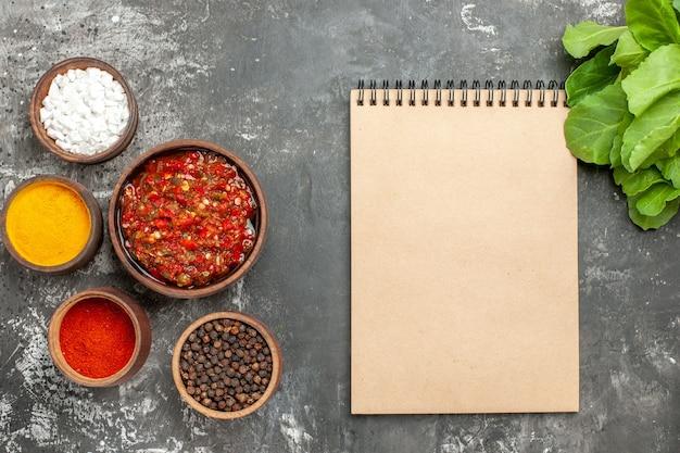 Vista superior deliciosas especiarias diferentes adjika em pequeno bawls um caderno sobre fundo cinza