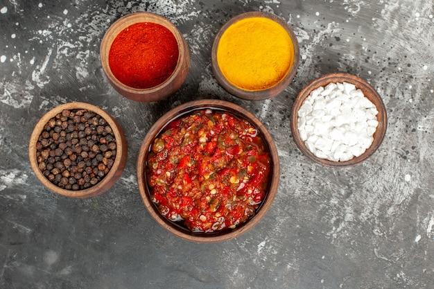 Vista superior deliciosas especiarias diferentes de adjika em pequenos gritos em fundo cinza