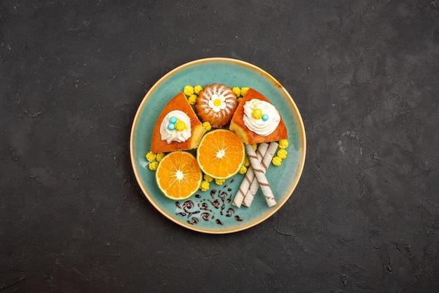 Vista superior deliciosas fatias de bolo com biscoitos e tangerinas fatiadas em um fundo escuro torta de frutas cítricas bolo biscoito chá doce