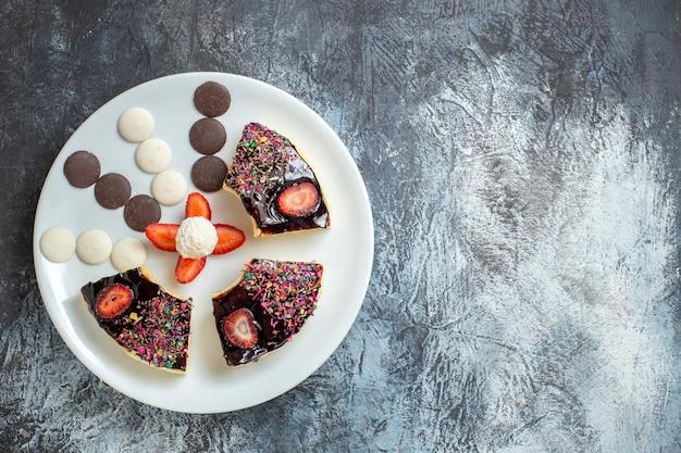 Vista superior deliciosas fatias de bolo com bolinhos na superfície escura