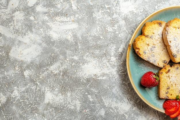 Vista superior deliciosas fatias de bolo com frutas em uma superfície clara torta de bolo de frutas doces