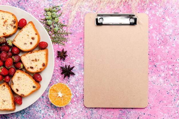 Vista superior deliciosas fatias de bolo com morangos vermelhos frescos e bloco de notas na mesa rosa bolo assar biscoito doce cor torta biscoito de açúcar
