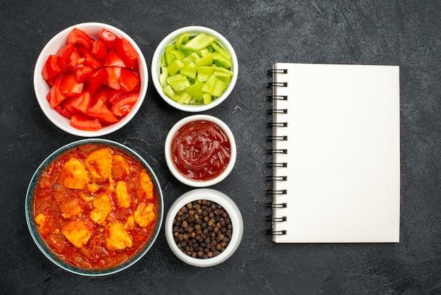 Vista superior deliciosas fatias de frango com molho de tomate e vegetais frescos em fundo escuro prato de molho de frango carne de tomate