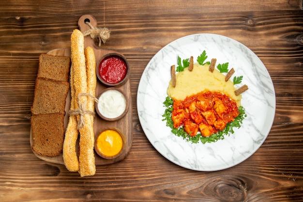 Vista superior deliciosas fatias de frango com purê de batatas, pão e temperos na mesa de madeira refeição de batata comida pimenta picante