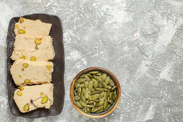 Vista superior deliciosas fatias de torrão com sementes verdes em fundo branco