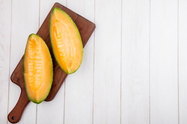 Vista superior deliciosas fatias frescas de melão melão na placa de cozinha de madeira em madeira branca com espaço de cópia