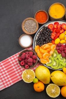 Vista superior deliciosas frutas fatiadas dentro do prato com frutas frescas na fruta escura foto exótica árvore madura vida saudável