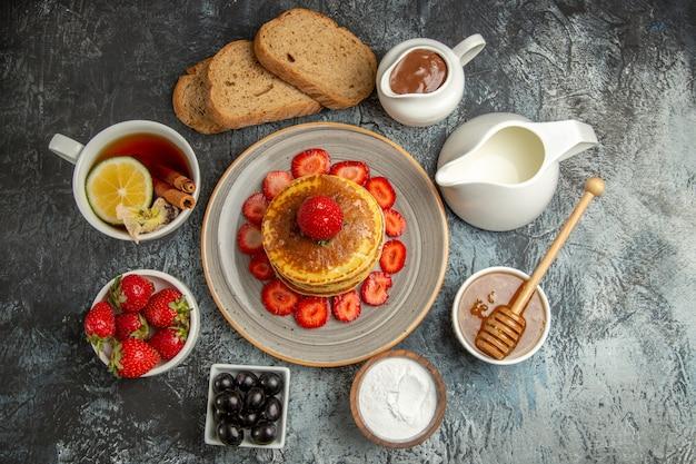 Vista superior deliciosas panquecas com chá e frutas na luz