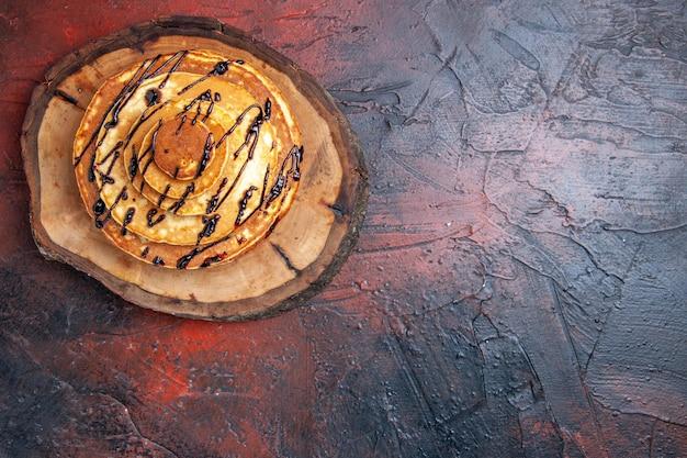 Vista superior deliciosas panquecas com cobertura em superfície escura