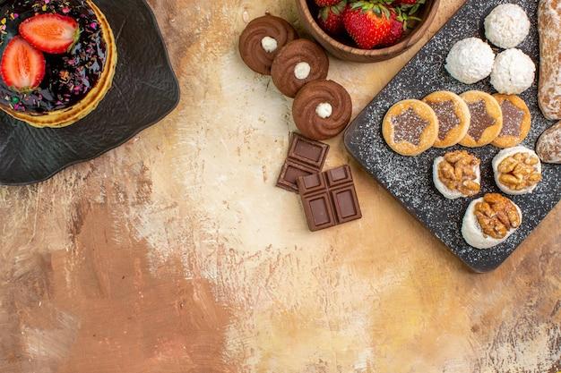 Vista superior deliciosas panquecas com doces e biscoitos na superfície de madeira