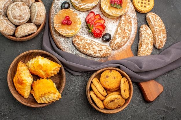 Vista superior deliciosas panquecas com frutas e bolos doces na mesa escura